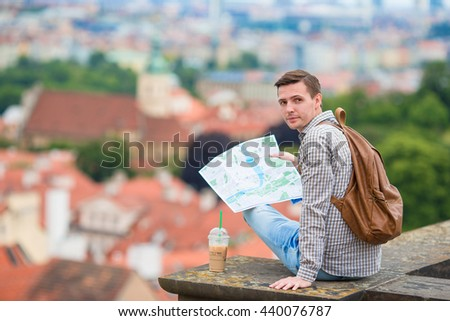 Young man with a city map and backpack background european city. Caucasian tourist looking at the map of European city with beautiful view of attractions. - stock photo