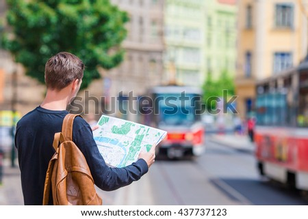 Young man with a city map and backpack in Europe. Caucasian tourist looking at the map of European city in search of attractions. - stock photo