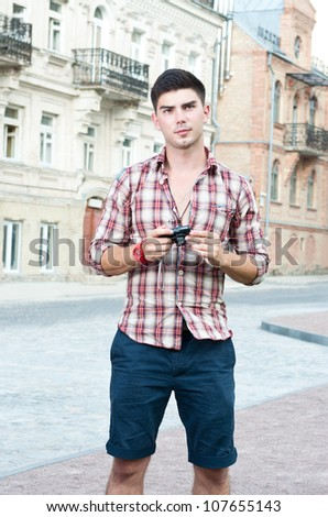Young man with a compact camera stands on the street. - stock photo