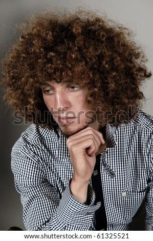 Young man with a curly hair on a gray background - stock photo
