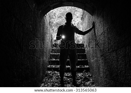 Young man with a flashlight enters the stone tunnel and looks in the dark, monochrome photo - stock photo