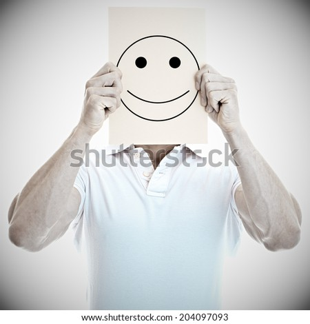 Young man with a happy smiley card covering face  - stock photo