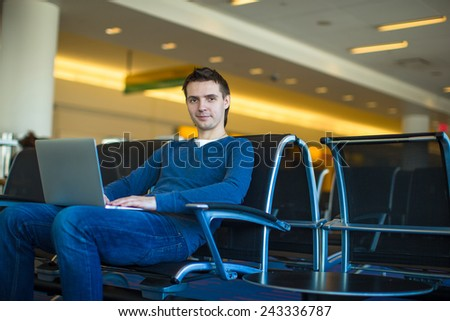 Young man with a laptop at the airport while waiting his flight - stock photo