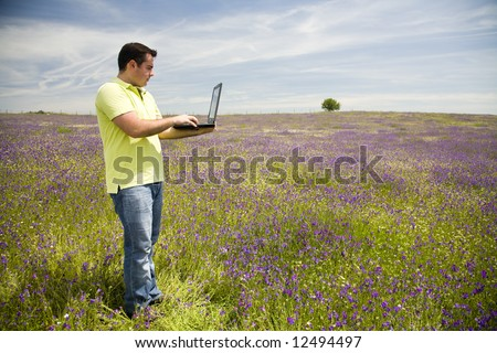 young man with a laptop computer on a flower field - stock photo