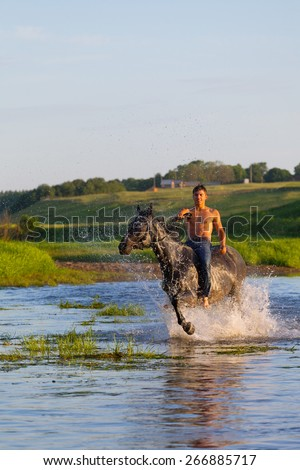 young man with a naked torso jumps astride a horse through the river - stock photo