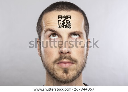 young man with a qr code on his forehead - stock photo