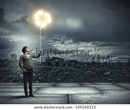 Young man with a recycle symbol against a polluted and ruined landscape - stock photo
