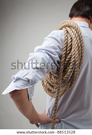 young man with a rope on his shoulder - stock photo