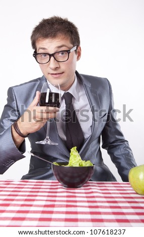 Young man with a salad drinking wine. - stock photo