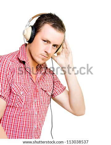 Young man with a serious expression in a red checked shirt wearing a pair of large wired circumaural headphones isolated on white - stock photo