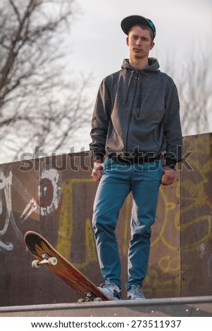 Young man with a skateboard standing on top of the skate ramp - stock photo
