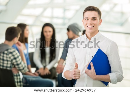 Young man with a tablet and a group of people in the background. - stock photo