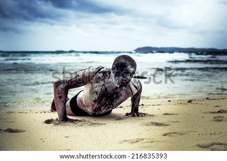 young man with a zombie body painting, covered with blood on the beach  (halloween topic) - stock photo