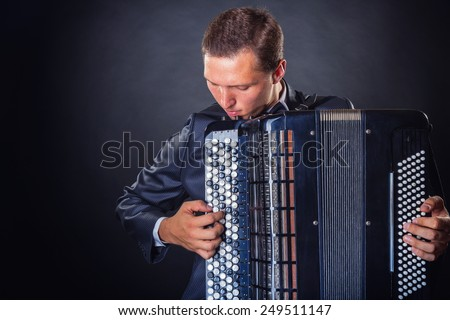 Young man with accordion on a black background with copy space - stock photo