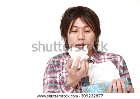 young man with an allergy sneezing into tissue - stock photo