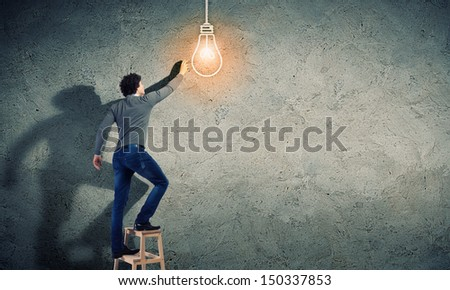 Young man with an electric light bulb against the wall - stock photo