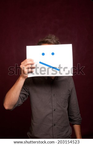 Young man with an sceptical slash smiley card covering face - stock photo