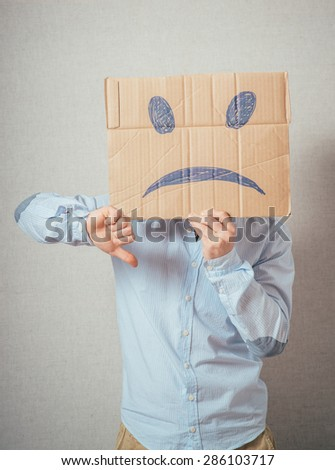 Young man with an unhappy smiley card half covering face - stock photo