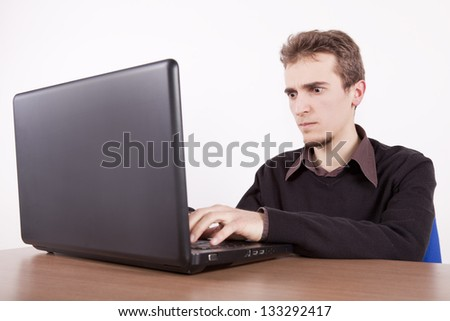 young man with angry face using a laptop at a desk - stock photo