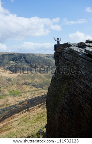Young man with arms outstretched sitting on cliff's edge and looking to a sky with clouds. - stock photo