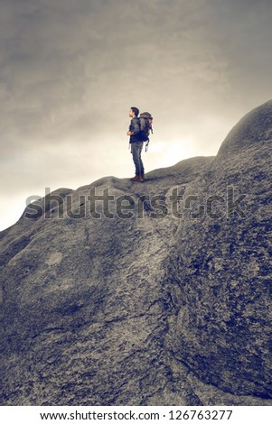 young man with backpack hiking in the mountains - stock photo