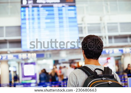 Young man with backpack in airport near flight timetable - stock photo