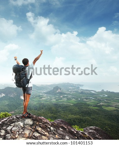 Young man with backpack standing with raised hands on top of a mountain and enjoying valley view - stock photo