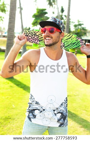 Young Man with bag and cap,Travel Lifestyle concept with city on background.Sunshine portrait of young hipster,with board and travel bag,opposite palms.Swag man,hipster man in swag outfit,cool beard - stock photo