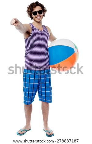 Young man with beach ball and pointing to camera - stock photo