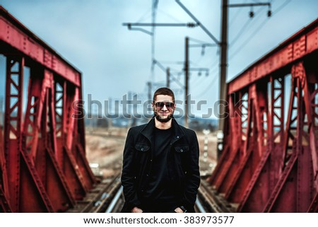 Young man with beard walking on the railway - stock photo