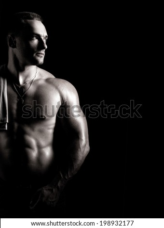 young man with beautiful musculature standing on dark background - stock photo