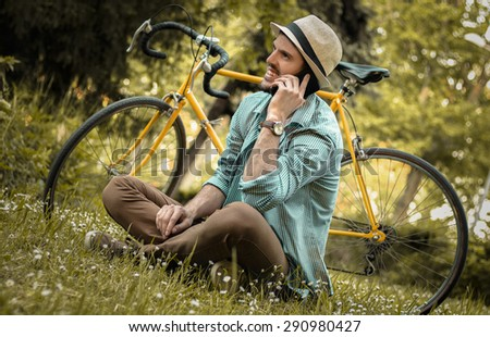 Young man with bicycle taking a break, talking on the phone in a park. Cyclist resting.  - stock photo