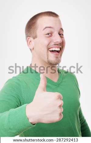 young man with big toothy smile making thumbs up gesture - stock photo