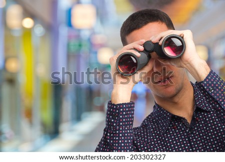 young man with binoculars in a shopping center - stock photo