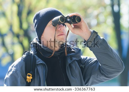 Young man with binoculars is bird watching at demi-season natural background - stock photo