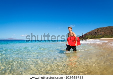 Young Man with Boogie Board at the Beach - stock photo