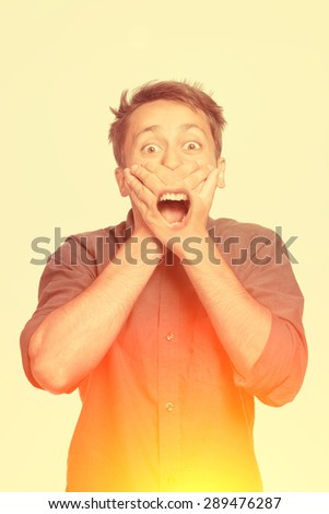 Young man with both hands closing mouth, isolated - stock photo