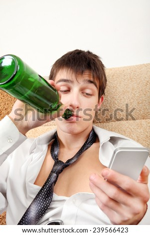Young Man with Bottle of the Beer and Cellphone on the Sofa at the Home - stock photo