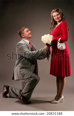 Young man with bouquet of roses stand on one knee in front of beautiful girl - stock photo