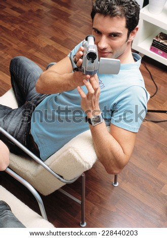Young man with camcorder - stock photo