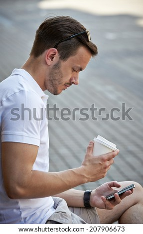 young man with coffee cup sitting and looking on smart phone - stock photo