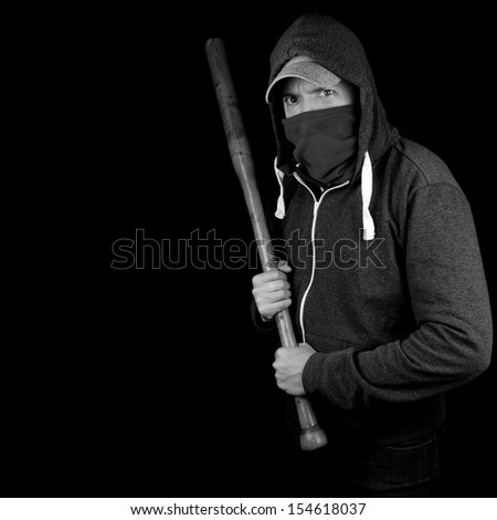 Young man with covered face, holding baseball bat, threatening, waiting to attack. Isolated in black and white with copy space. - stock photo