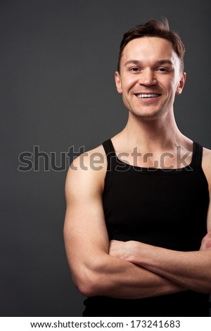 Young man with crossing arms against gray background - stock photo