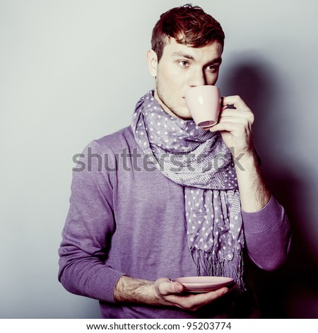 Young man with cup of coffee in his hands - stock photo