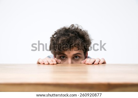 Young man with curly hair peeking from behind the desk - stock photo