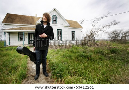 Young man with curly hair standing in front of an abandoned house holding a guitar case. - stock photo