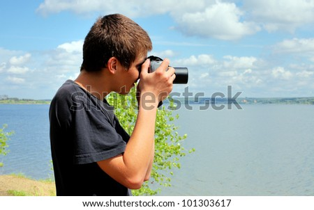young man with digital photo camera aiming outdoor - stock photo