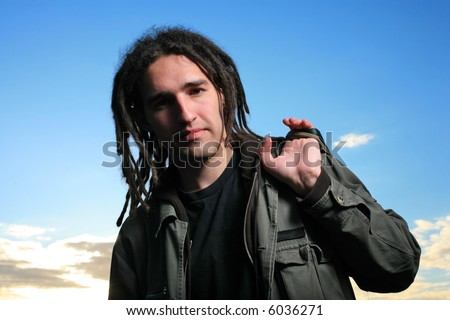 Young man with dreadlocks over blue sky - stock photo