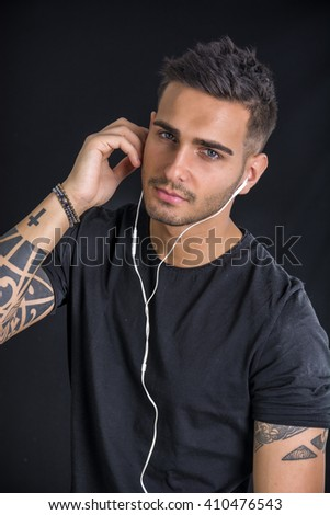 Young man with earphones listening to music - stock photo