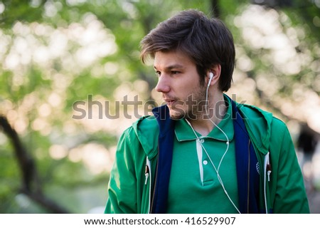 Young man with earphones listening to music. Portrait of young person in the park, who is thinking about something. - stock photo
